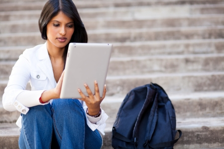 young female college student using tablet computer outdoors photo