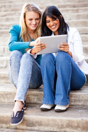 two young female college friends using tablet computer together outdoors photo