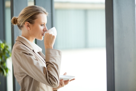 beautiful young businesswoman drinking coffee in office photo