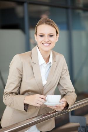 beautiful female white collar worker having coffee break at work photo