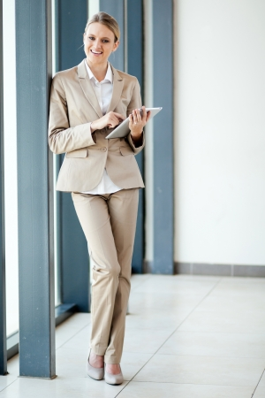gorgeous businesswoman: happy young businesswoman full length portrait with a tablet computer