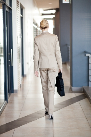 rear view of young businesswoman walking to office photo