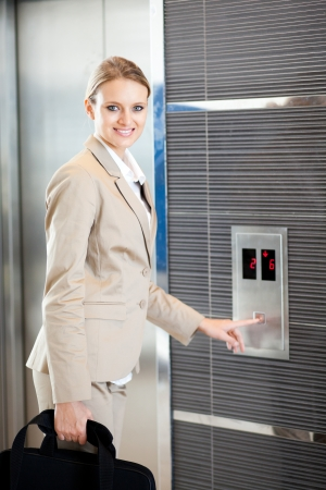 people in elevator: beautiful young businesswoman using elevator