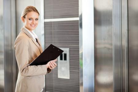 magabiztos: fiatal, üzletasszony várja lift az épületben