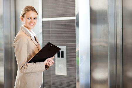 people in elevator: young businesswoman waiting for elevator in the building