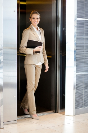 beautiful young businesswoman walking out elevator photo