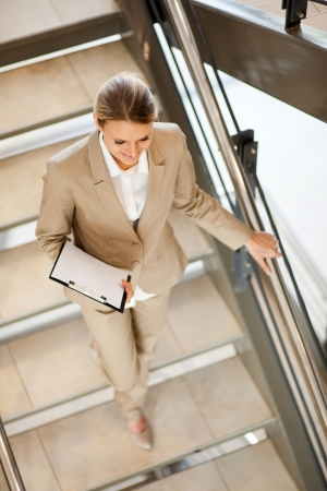 attractive young businesswoman walking down stairs photo