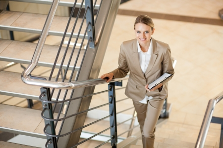 cute young businesswoman walking up stairs photo
