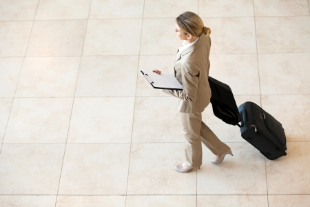 young businesswoman walking at airport with luggage photo