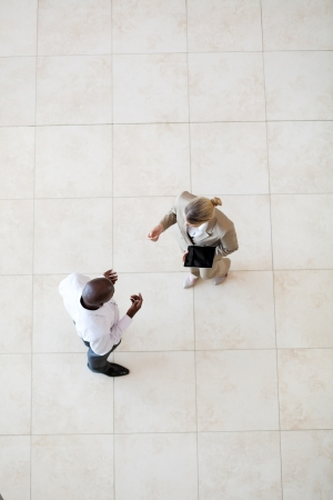 overhead of african american businessman talking to businesswoman at lobby photo