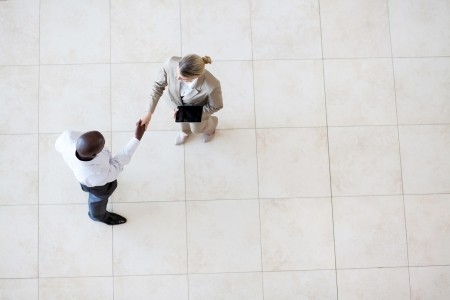 businessman and businesswoman handshake at office lobby