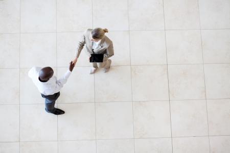 african american handshake: businessman and businesswoman handshake at office lobby