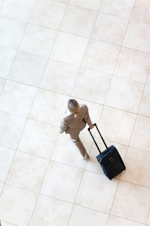 overhead view of young businesswoman walking at airport photo