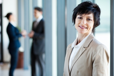 middle aged businesswoman in office with colleagues at background photo