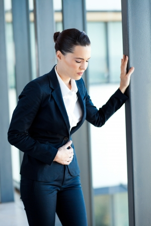 young businesswoman having period pain in office photo