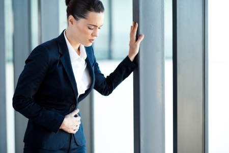 upset stomach: young businesswoman having stomach ache in office