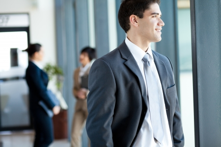 handsome young businessman looking outside office window photo