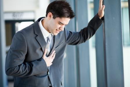 dolor en el pecho: hombre de negocios joven que tiene un ataque al coraz�n o dolor en el pecho