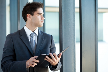 good looking man: thoughtful young businessman with tablet computer
