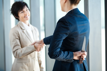 daangerous businesswoman holding knife behind her back while handshake Stock Photo - 14899028