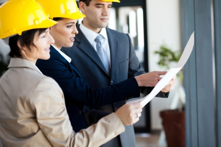 white collar workers: group of construction managers looking at blue print
