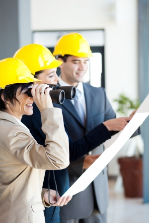 architect looking at construction site with binoculars photo