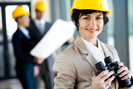 elegant middle aged female architect with binoculars photo