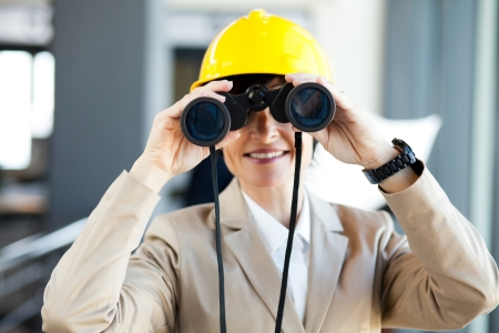middle aged female construction project manager using binoculars photo