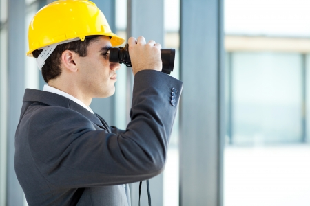 hat project: male architect looking at construction site with binoculars
