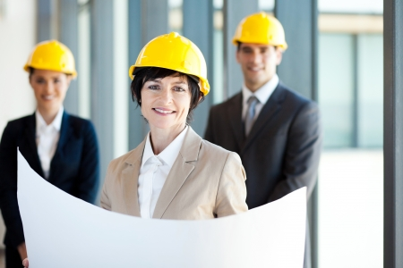 middle aged construction businesswoman holding blue print in front of colleagues photo