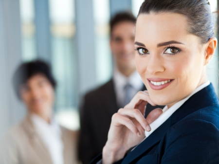 blue collar: attractive young businesswoman closeup portrait with co-workers in background