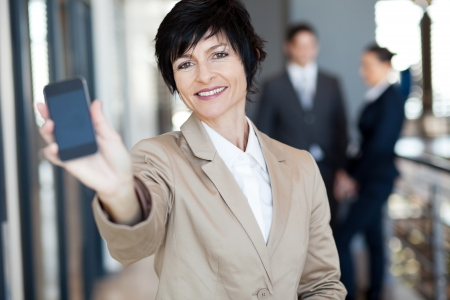 happy middle aged businesswoman showing smart phone Stock Photo - 14898916