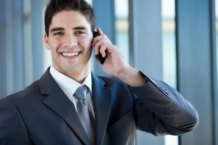 cell phone: happy successful young business man talking on cell phone
