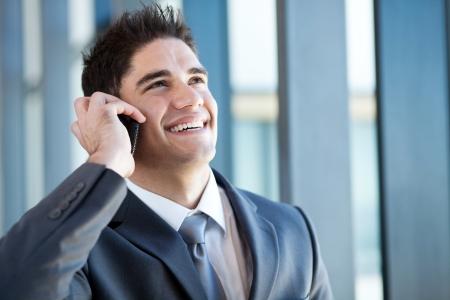 talking businessman: hombre de negocios joven feliz hablando por tel�fono m�vil