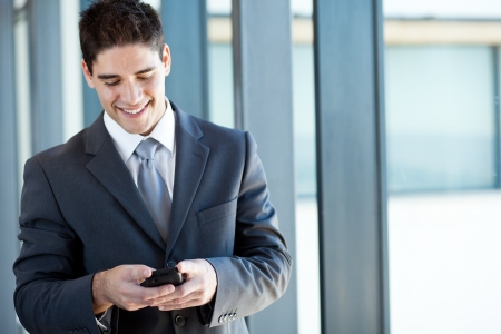 happy businessman reading emails from a smart phone photo