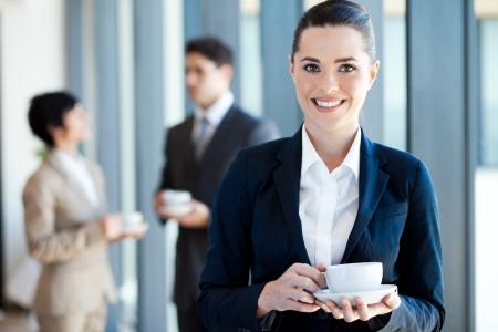 break from work: young businesswoman having coffee break at work