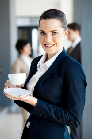 beautiful young businesswoman drinking coffee in office during break photo