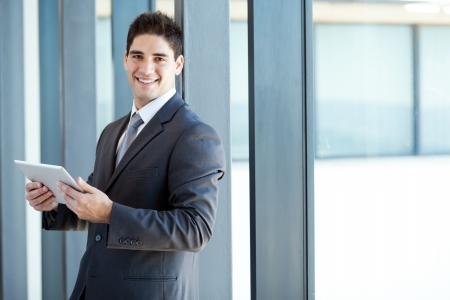 well dressed  holding: happy young businessman with tablet computer in office