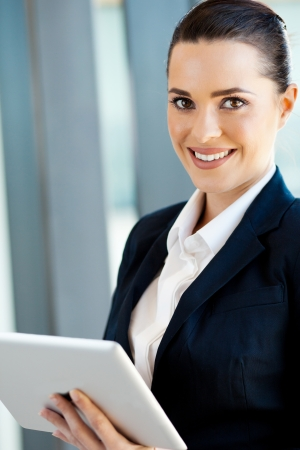 navy blue suit: beautiful young businesswoman with tablet computer in office