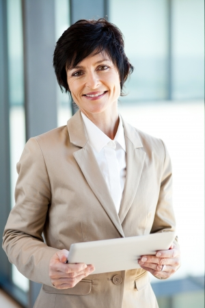 woman window: elegant middle aged businesswoman with tablet computer in office