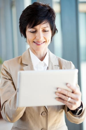 smart mid age businesswoman using tablet computer photo