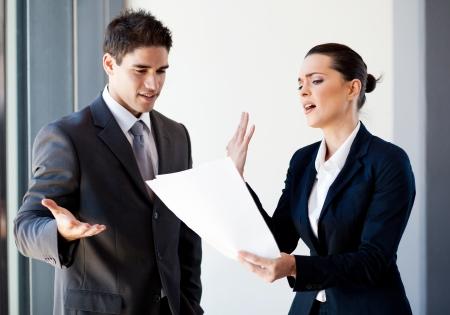 personas discutiendo: dos jóvenes colegas discutiendo sobre papeleo en la oficina
