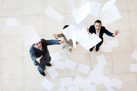 group of businessman and businesswoman catching papers falling from above photo