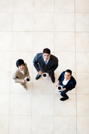 overhead view of colleagues having coffee break at work photo