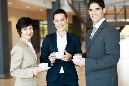 group of colleagues having coffee break at work photo