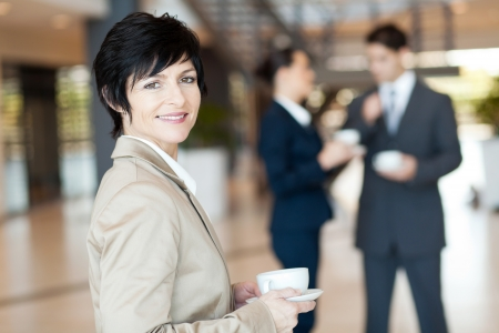middle aged businesswoman having coffee break photo