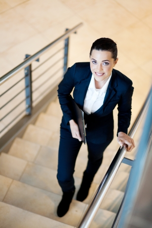gorgeous young businesswoman walking up stairs photo
