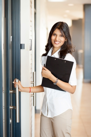 young businesswoman opening office door photo