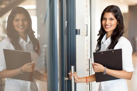 job opening: hermosa joven indio trabajador de cuello blanco apertura de la oficina puerta Foto de archivo