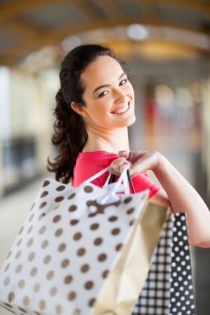 happy young woman carrying shopping bags in mall Stock Photo - 15402598